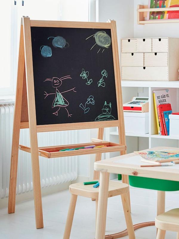 een krijtbord met tekening op in een klas met kleine tafel en stoeltjes met op achtergrond opbergaccessoires