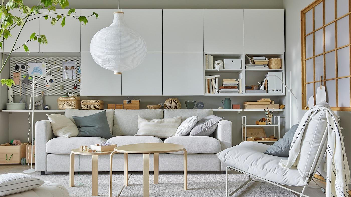 Een lichte woonkamer met een fauteuil, veel witte wandkasten en een ronde, witte hanglamp.