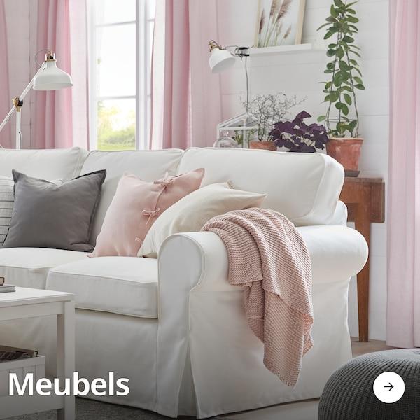 Een lichte woonkamer met roze gordijnen, een witte bank en allerlei woonaccessories zoals een lamp, kussentjes en een poef.