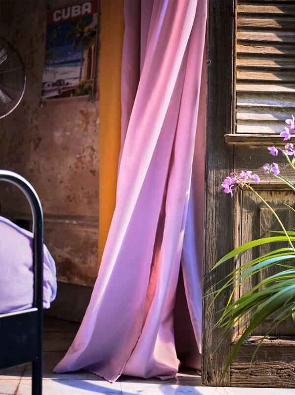 Een lichtpaars, luchtzuiverend gordijn wappert in de wind naast een houten luik.