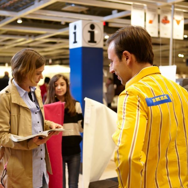 Een mannelijke IKEA medewerker staat enthousiast een vrouwelijke klant te hulp in de winkel. De vrouw heeft een boekje in de hand. Op de achtergrond staat een kind.