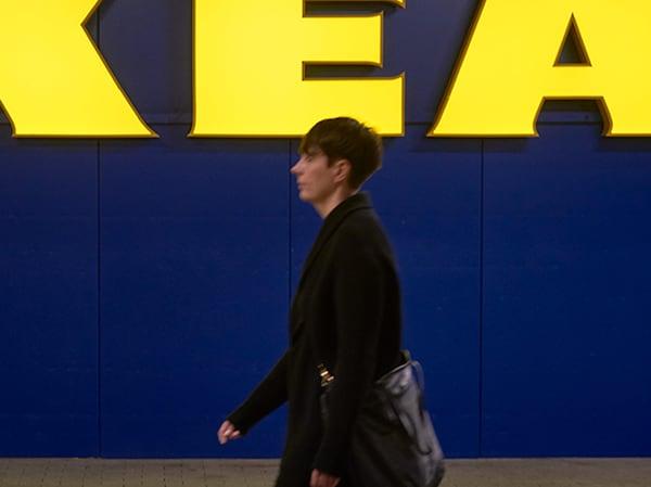 Een medewerker vóór een IKEA winkel die 's ochtends naar zijn werk gaat.
