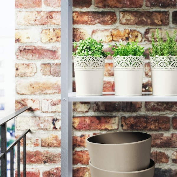 Een metalen buitenrek op een balkon met witte romantische bloempotjes gevuld met kruiden tegen een bakstenen muur