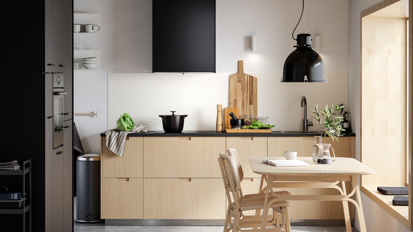 Een minimalistische keuken met ladefronten van licht bamboe, zwarte deuren, een eettafel van licht bamboe en twee stoelen.