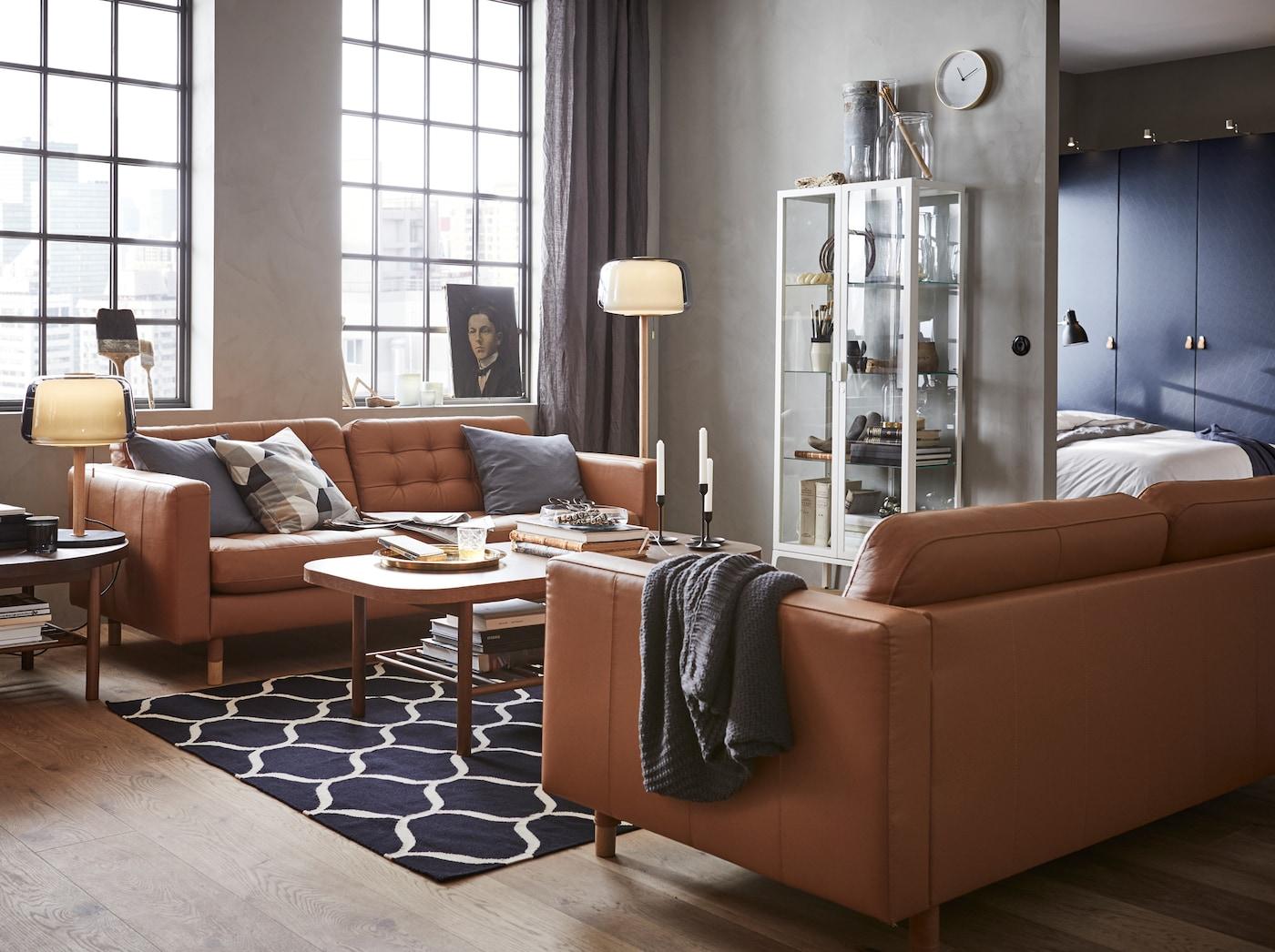 Een moderne woonkamer met MILSBO glazen opbergkast, LANDSKRONA bruine leren banken en ronde houten LISTERBY salontafel.