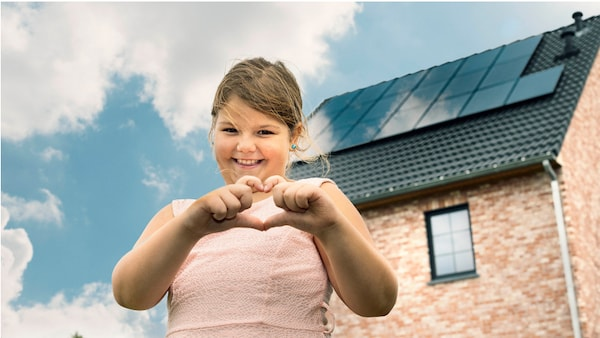 Een moie meisje vormt een hartje met haar handen voor een huis met zonnepanelen.