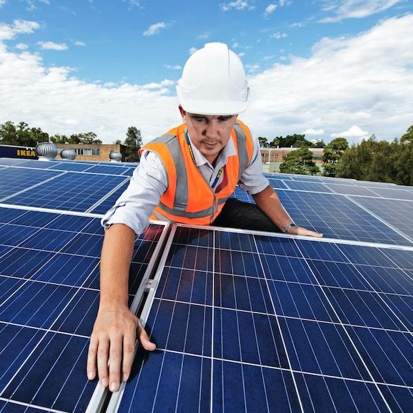 Een monteur installeert zonnepanelen