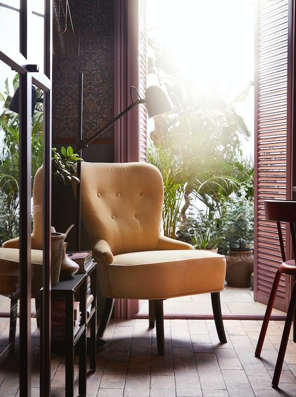 Een mosterdgele fauteuil bij een open deur naar een balkon vol planten, naast een lamp en een vitrinekast.