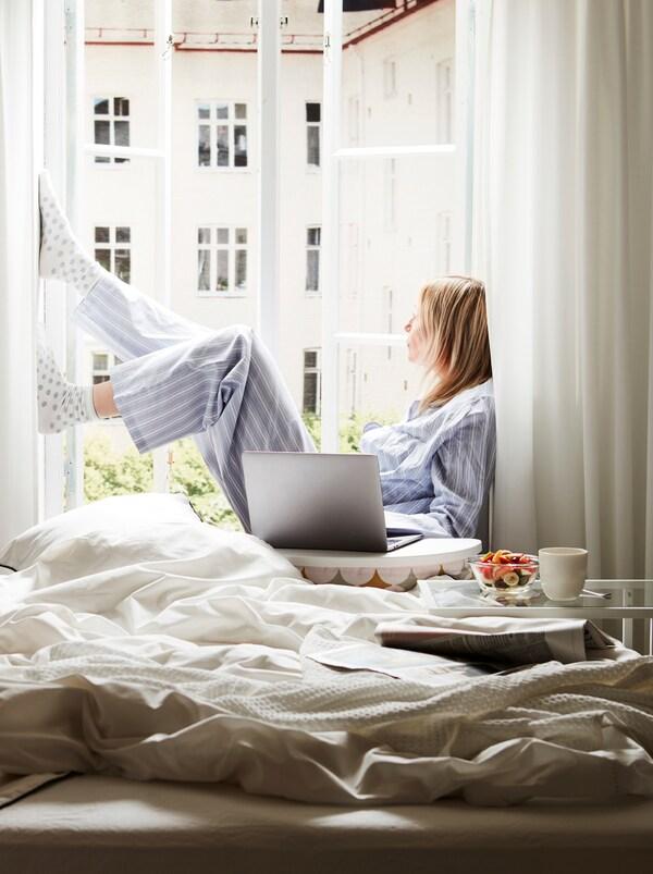 Een onopgemaakt bed naast een open, zonovergoten raam. Op de vensterbank zit een vrouw met een laptop op een BYLLAN steun naast haar.