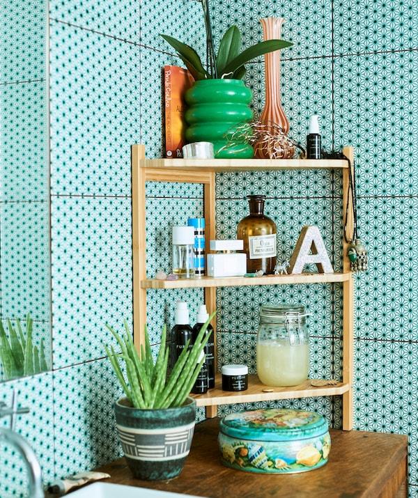 Een open hoekkast van bamboe met drie planken, kaarsen en planten, op een houten kast tegen groene badkamertegels.