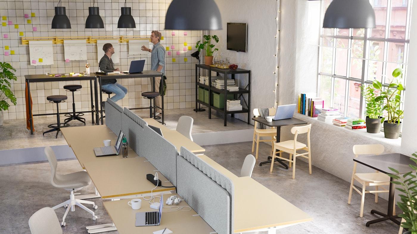 Een open kantoor met twee mannen die aan hoge tafels werken en een vrouw die op een beige/witte stoel aan een bureau zit en e-mails opstelt.