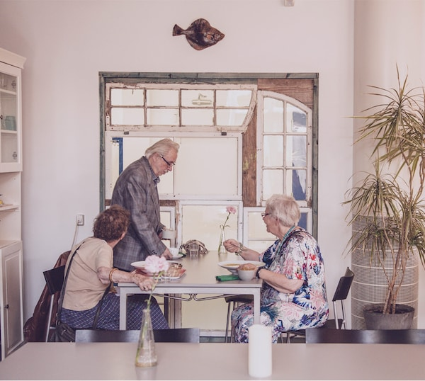 Een ouder koppel en hun vriendin lunchen samen in een eclectisch restaurant.