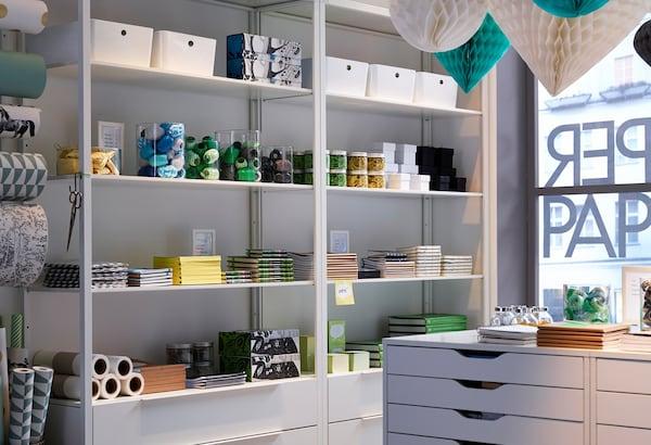 Een papierwinkel met witte muren en kleurrijke decoraties, white rekken en ALEX ladeblokken op wielen.