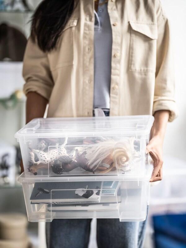 Een persoon met een beige open hemd draagt twee doorzichtige plastiek bakken gevuld met spullen.