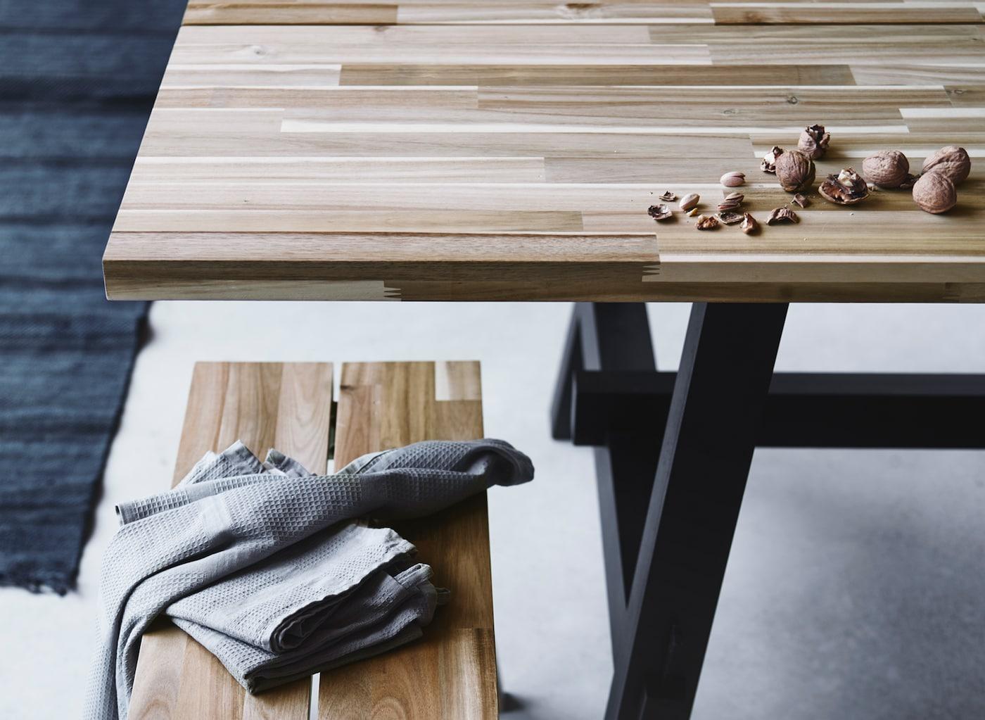Een rechthoekige SKOGSTA eettafel en bank in Skandinavische stijl, vervaardigd uit hout met een nerfpatroon en kleurvariaties.