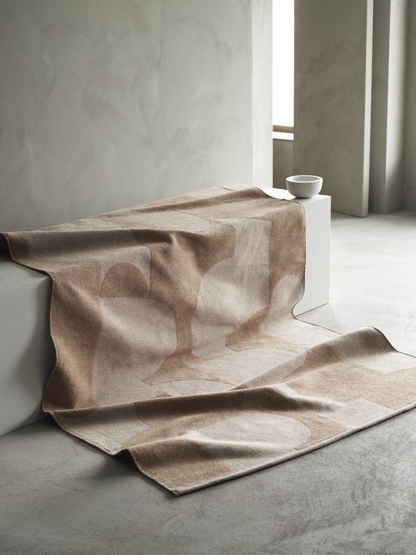 Een RÖDASK vloerkleed gedrapeerd op een betonnen trap zodat het grafische patroon en jacquardmotief duidelijk te zien is.