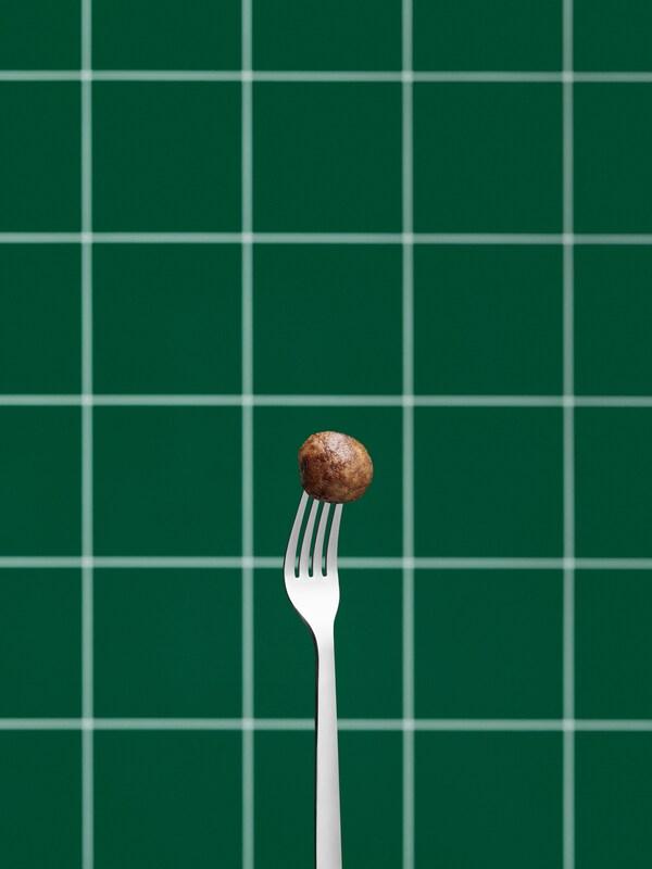 Een roestvrijstalen vork staat rechtop en prikt in een plantaardig Zweeds balletje. Op de achtergrond een groene betegelde wand.