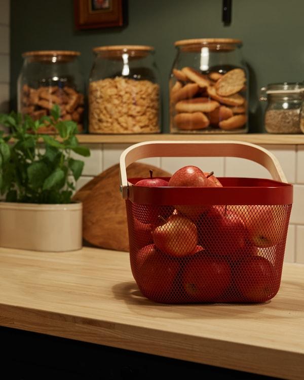 Een rood mandje op een keukenwerkblad gevuld met rode appels, op de achtergrond staan verschillende glazen potten met eten erin.