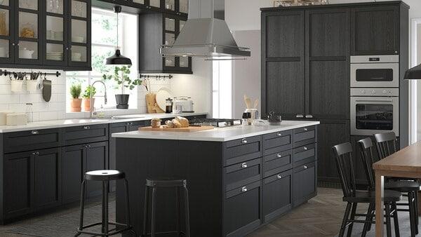 Een ruime zwart-witte keuken in een klassieke stijl met zwart gebeitste LERHYTTAN kastdeuren.
