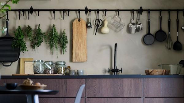Een SINARP keuken met een tafel en stoelen, een HULTARP rail en een haak hangen aan de muur.