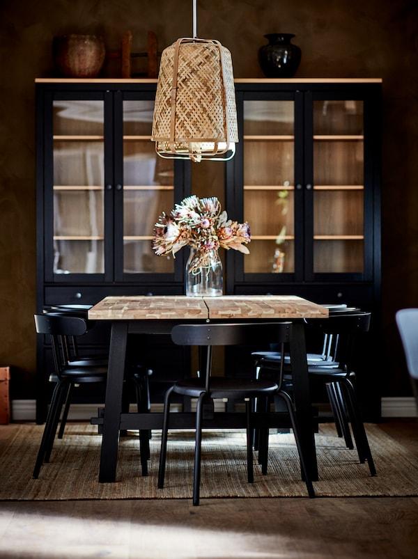 Een SKOGSTA eettafel met een vaas met bloemen onder een KNIXHULT hanglamp, met daaromheen donkere stoelen. Zwarte kasten staan tegen de muur.