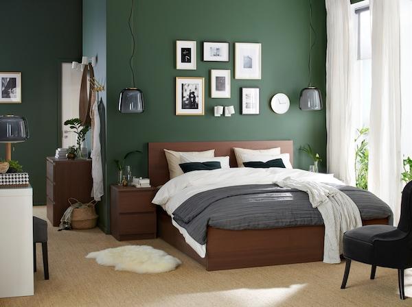 Een slaapkamer met een bedframe en nachtkastje in bruin gebeitst essenfineer, een witte kaptafel en een grijze fauteuil.