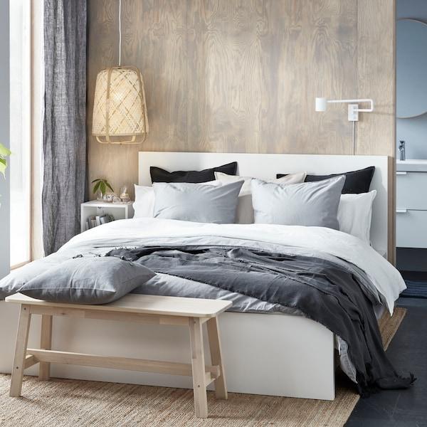 een slaapkamer met een bedframe met een dekbedovertrek en plaid, een bankje voor het bedframe