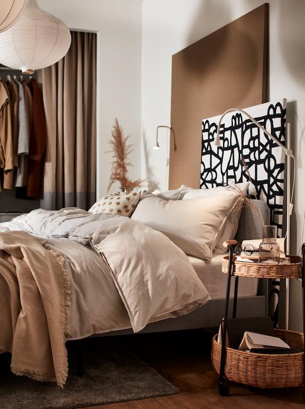 Een slaapkamer met een grijs SLATTUM gestoffeerd bedframe en beige BERGPALM dekbedovertrekken en kussenslopen.