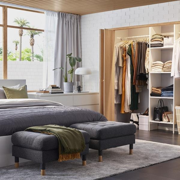 Een slaapkamer met een ingebouwde garderobekast, een wit bedframe, een witte ladekast en twee donkergrijze voetenbankjes