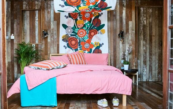 Een slaapkamer met houten lambrisering en een bed met roze beddengoed, een bedhemel van kleurrijke stof en planten naast het bed.