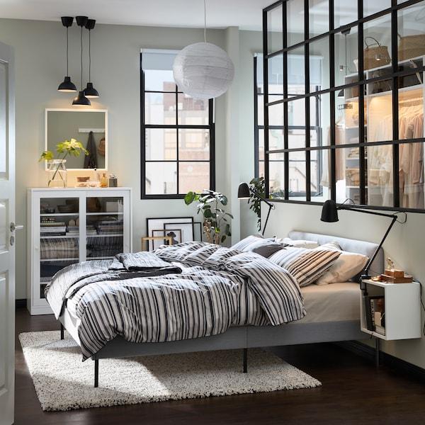 Een slaapkamer mt een gestoffeerd, grijs bedframe, een grijs vloerkleed, een witte kast met glazen deuren en zwarte lampen.