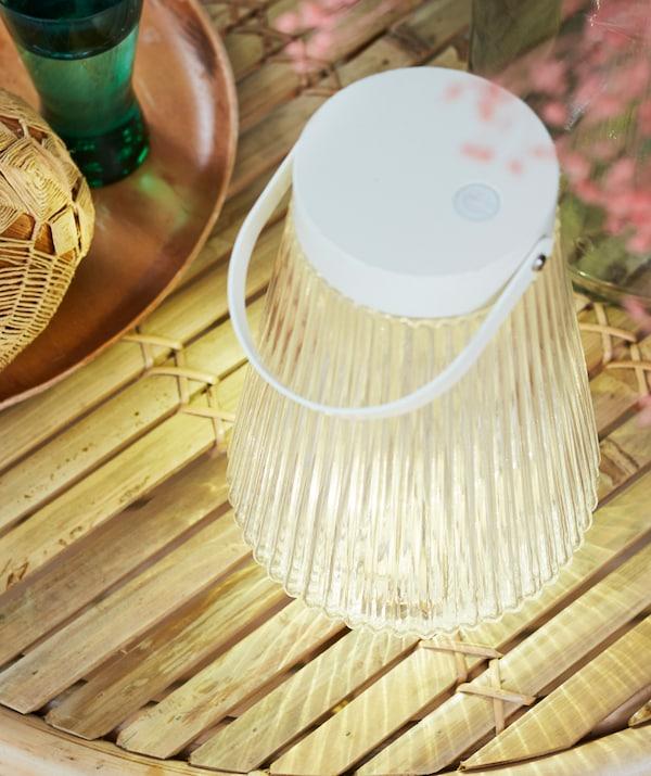 Een SOLVINDEN staande lamp op zonne-energie staat naast een dienblad op een tafelblad gemaakt van dunne houten latten. De lamp verspreidt zacht licht.