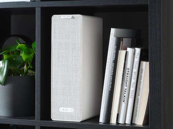 Een SYMFONISK boekenplankspeaker op een boekenplank, samen met een aantal boeken.