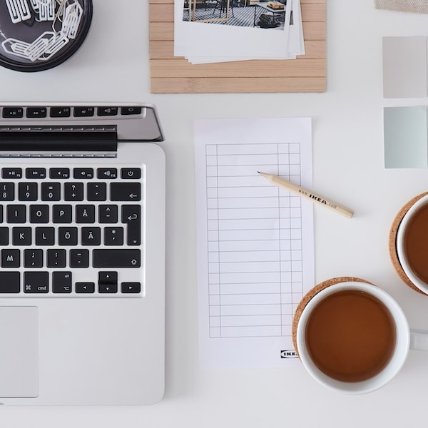 Een tafel met twee kopjes thee, een computer, een notitieboekje en verschillende vierkante kleurstalen