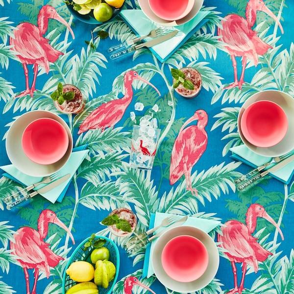 Een tropische tafel met gekleurd servies en een tafelkleed met flamingo's en palmen.