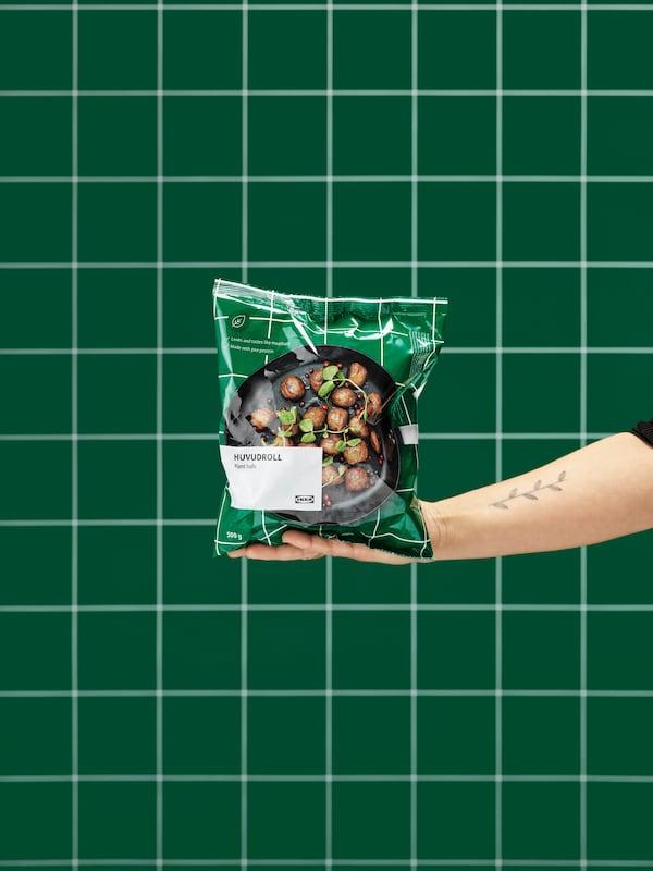 Een uitgestrekte hand houdt een ongeopende zak HUVUDROLL plantaardige balletjes vast. Een groen betegelde wand op de achtergrond.