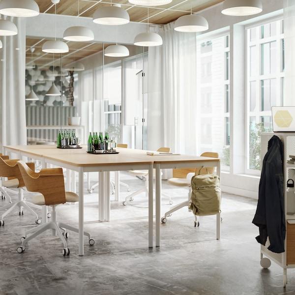 een vergaderruimte met vergaderstoelen, veel hanglampen aan plafond