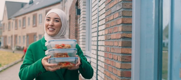 Een vrouw die lacht heeft drie voedselopbergbakjes in haar hand.