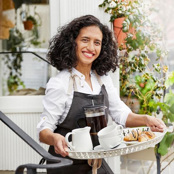 Een vrouw met een schort draagt een dienblad met gebak, kopjes, een kan en een koffiemaker naar buiten. Op de achtergrond zijn planten.
