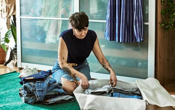 Een vrouw met getatoeëerde armen zit in een slaapkamer op een groen tapijt terwijl ze een stapel jeans in een stoffen zak stopt.