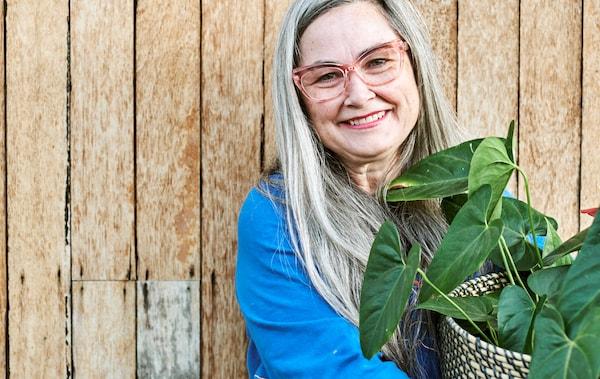 Een vrouw met lang grijs haar, met een bril met roze montuur en blauwe top, glimlacht en houdt een bladplant in een gevlochten plantenpot vast.