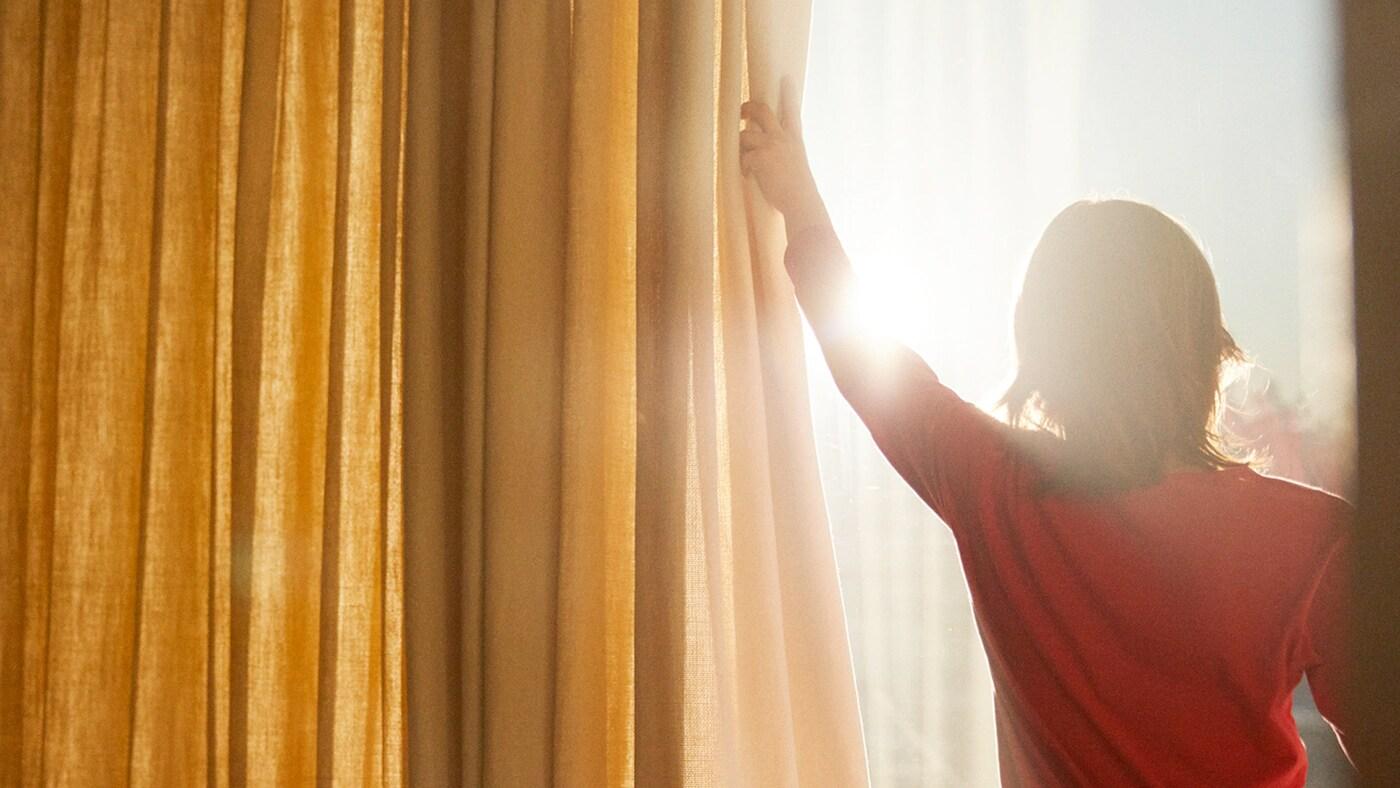 Een vrouw opent de gordijnen en de zon schijnt naar binnen