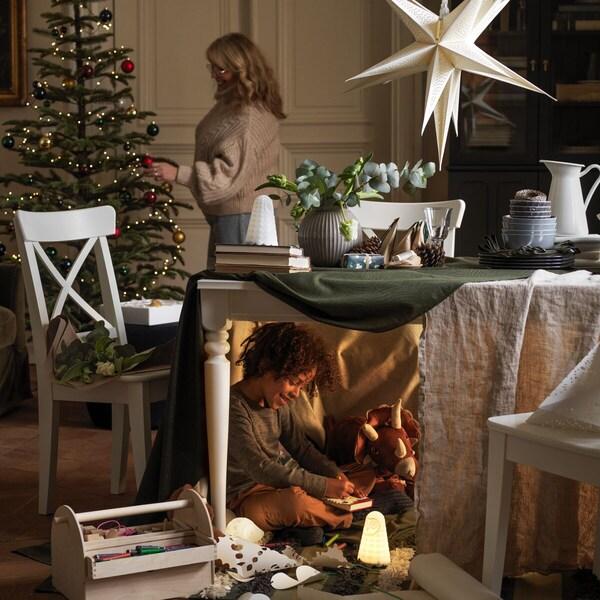 Een vrouw versiert een boom, terwijl onder de tafel op de voorgrond een half verborgen jongen speelt met zijn speelgoed.