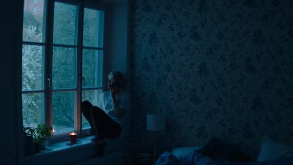 Een vrouw zit 's nachts op de vensterbank van een slaapkamer te bellen. Naast haar brandt een OSYNLIG kaars.