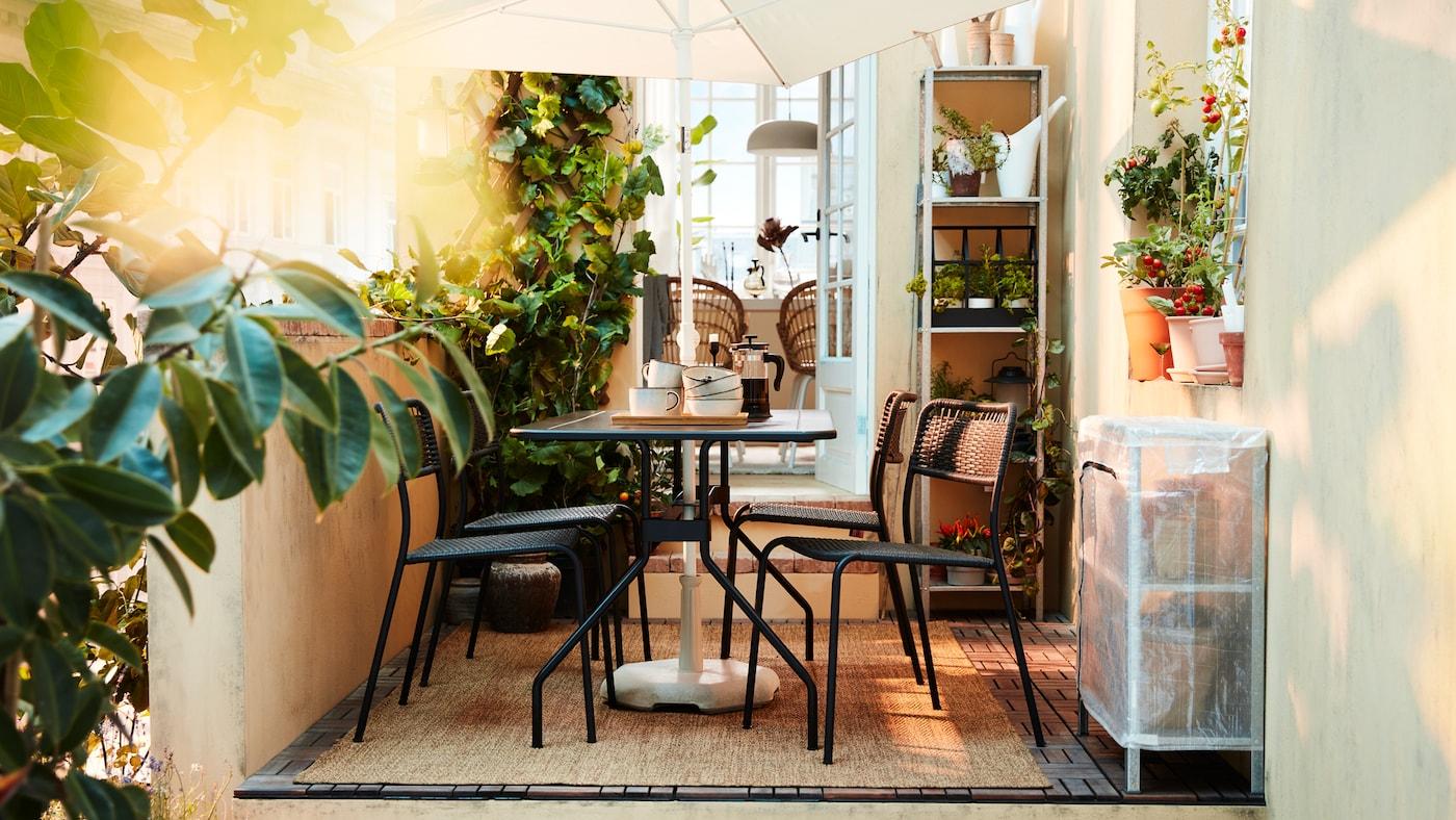 Een weelderige buitenruimte met zwarte eetmeubels, een witte parasol, heel wat planten en een geweven tapijt.
