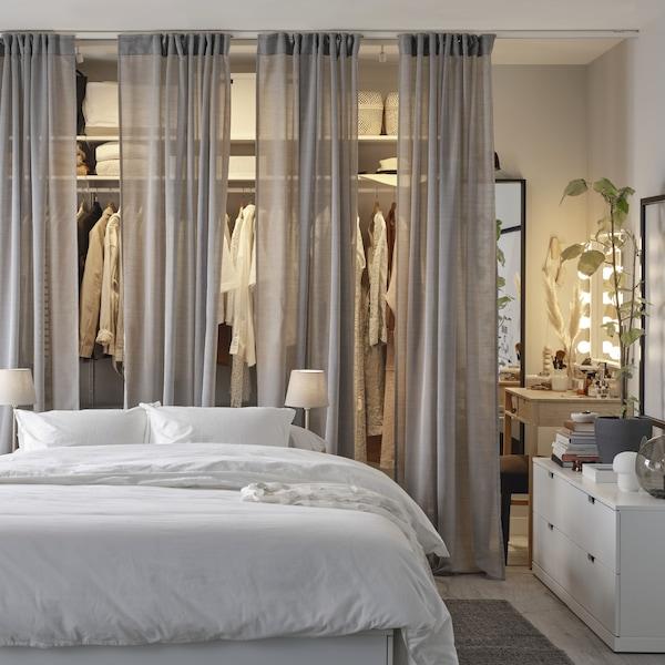 Een wit bedframe, een witte kist, een grijs kleed en een open garderobekast die half verstopt gaat achter grijze gordijnen.