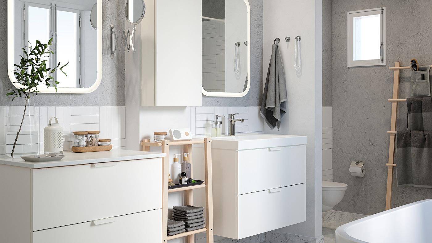 Een wit betegelde badkamer met grijze muren, twee wastafels, spiegels en een rek in berkenhout met handdoeken en schoonheidsproducten.
