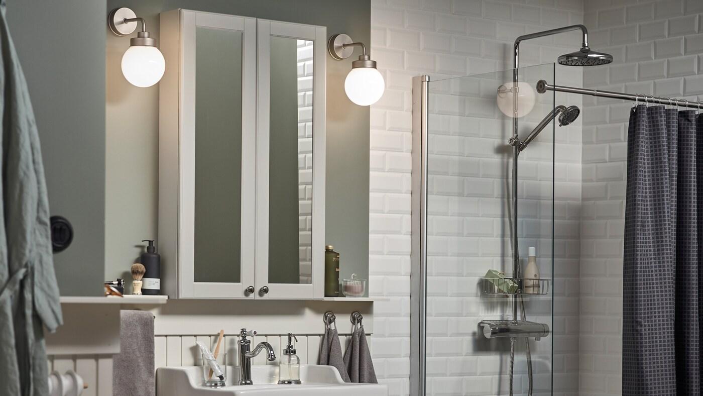 Een wit betegelde badkamer met lichtgroene muren, twee FRIHULT wandlampen aan weerszijden van een GODMORGON spiegelkast.