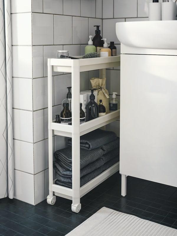 een wit plastiek rekje gevuld met badkamerspullen dat naast een lavabomeubel staat tegen een witte tegelmuur op een zwarte vloer.