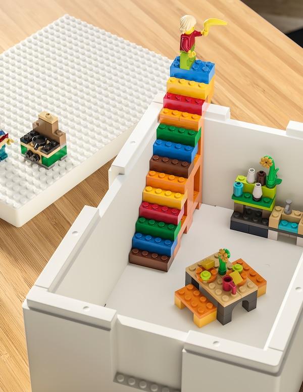 Een witte BYGGLEK box staat op een tafel, met felgekleurde LEGO-constructies, inclusief een set trappen, erin.